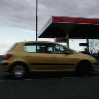 car speeding past a petrol station